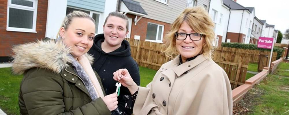 A Livin Staff member handing over the keys to two people outside their new property
