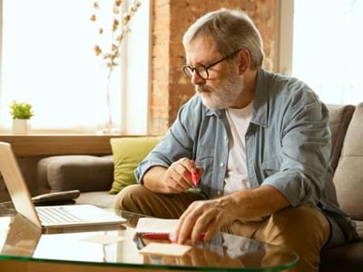 A man browsing on his laptop writing notes onto a piece of paper