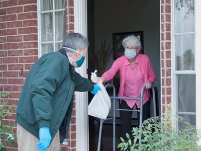 A man delivering food to an elderly woman on her doorstep
