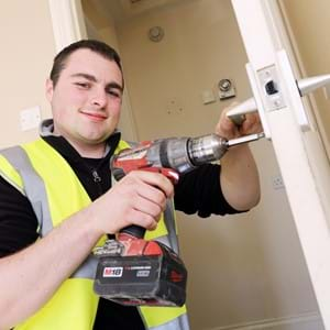 A work experience worker fixing an internal door