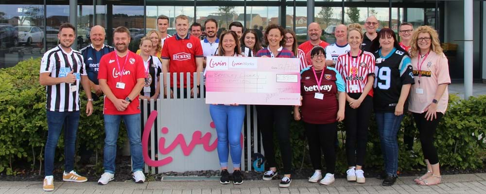 Livin's Bradley Lowery charity day featuring staff members in football tops holding a large cheque